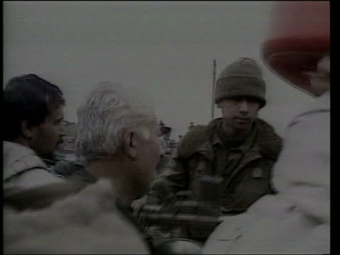 vídeos de stock, filmes e b-roll de day 3 lunchtime news bulletin lib 1991 seq soldiers trying to control mass evacuation of kurdish refugees into turkey - curdo