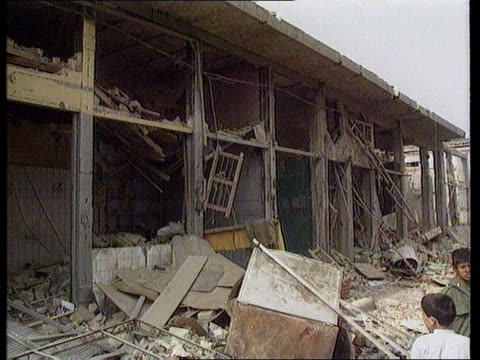 allied bombings in fallujah; subject to iraqi censorship iraq: fallujah: wrecked `souk' market place being shown to cameraman as people milling about... - al fallujah stock videos & royalty-free footage