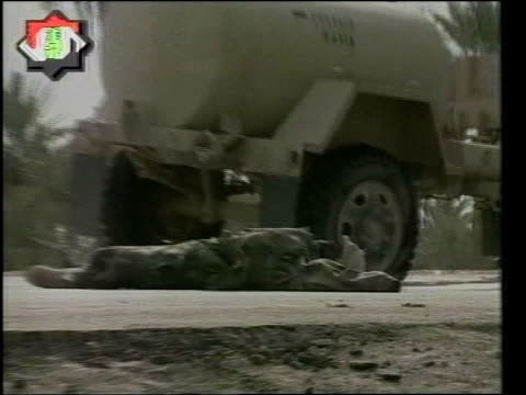 day 4 channel 4 news iraq nasiriyah ext onscreen logo body of us soldier lying beside military vehicle zoom tms bodies of dead american soldiers on... - nasiriyah stock-videos und b-roll-filmmaterial