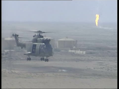 day 4 channel 4 news uk pool west of basra rumaila military helicopter flying over rumaila oil field air view small fire in oil field air to air... - iraq war stock videos and b-roll footage