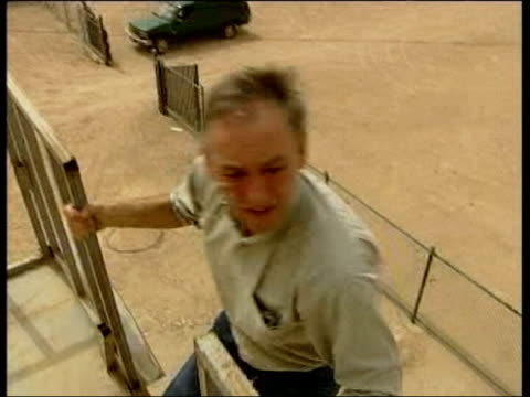 evening news; lib iraq: southern iraq ext itv news reporter terry lloyd climbing onto roof and looking through binoculars - itv evening news stock-videos und b-roll-filmmaterial