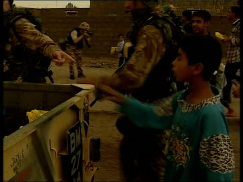 news at ten; pool umm qasr children along carrying water bottle children waving to british marines marines along with trailer distributing ration... - cetacea stock videos & royalty-free footage