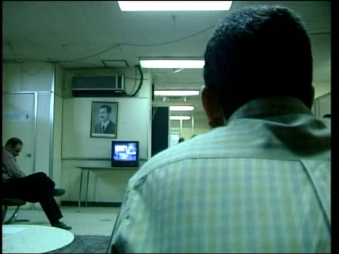 evening news; itn for itv iraqi men watching tv in room - itv evening news stock-videos und b-roll-filmmaterial