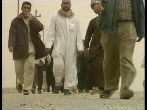 news at nine; itn pool iraq: basra ext gvs iraqi refugees towards along road as fleeing city british warrior apc demolishing mural of saddam hussein... - iraq stock videos & royalty-free footage