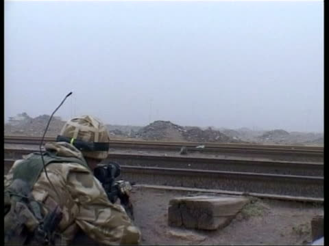 news at ten; pool iraq: basra ext british challenger tanks along british soldiers crouching in positions iraqi civilians leaving on back of truck... - civilian stock videos & royalty-free footage