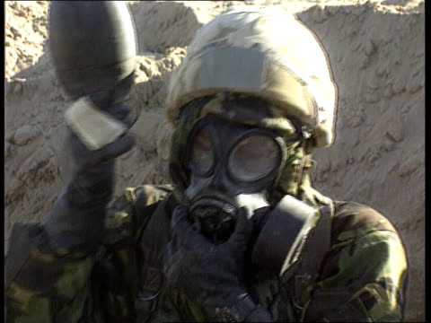 gulf war syndrome itn lib persian soldier in desert in nbc suit drinking from water bottle using tube soldier in nbc suit patrolling near camouflaged... - nbcuniversal video stock e b–roll