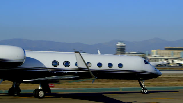 vidéos et rushes de gulfstream 550 private, corporate jet taxis on runway with lax control tower and theme restaurant in background - piste d'envol