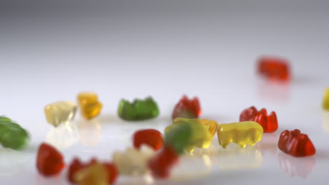 gummy bears drop on a white surface in slow motion. - 注意欠陥過活動性障害点の映像素材/bロール