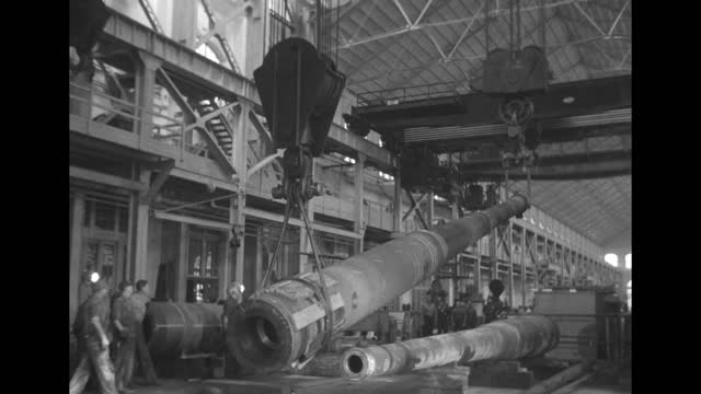gun barrel rotating on machine / various shots barrel hoisted up on both ends held by ceiling crane with one end rising, workers on sides / note:... - gun barrel stock videos & royalty-free footage