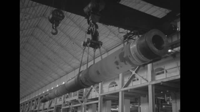 gun barrel suspended from ceiling crane slowly moving / turning machine wheels connected to maybe crane / pan wheels / barrel moving on crane / note:... - gun barrel stock videos & royalty-free footage