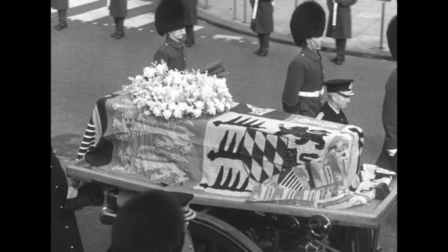 gun carriage bearing queen mary's coffin passes at far left as procession passes the cenotaph en route to westminster hall where the queen will lie... - victoria tower stock-videos und b-roll-filmmaterial
