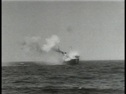 Gun crew firing deck cannons from UBoat WS Shell hitting freighter at sea explosion HA WS UBoat firing deck guns WS Smoking freighter ship World War...