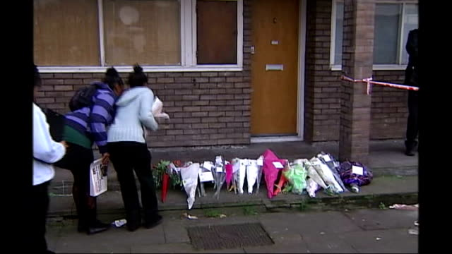 gun crime task force set up after third teenager shot in south london; friends mourning and laying flowers outside front door hand-made tribute sign... - street name sign video stock e b–roll