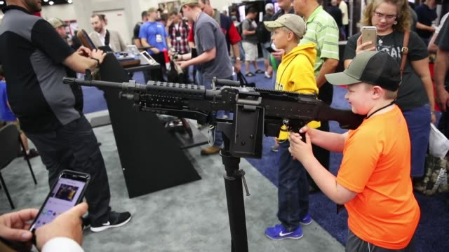 gun enthusiasts look over an m240 machine gun displayed by the manufacturer during the nra annual meetings exhibits on may 21 2016 in louisville... - national rifle association stock videos & royalty-free footage