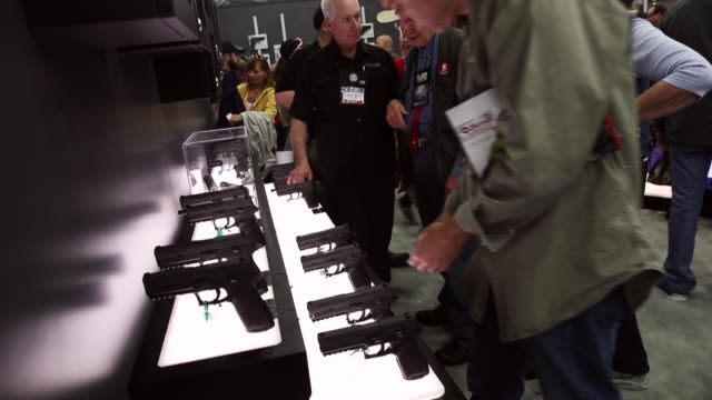 gun enthusiasts look over firearms at a vendor's booth during the nra annual meetings & exhibits on may 21, 2016 in louisville, kentucky. about... - 自衛点の映像素材/bロール