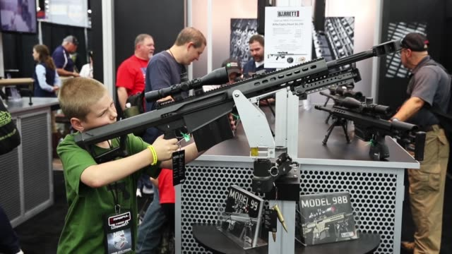 gun enthusiasts look over firearms at the barrett firearms manufacturing booth during the nra annual meetings exhibits on may 21 2016 in louisville... - national rifle association stock videos & royalty-free footage