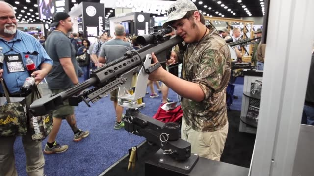 gun enthusiasts look over firearms at the barrett firearms manufacturing booth during the nra annual meetings & exhibits on may 21, 2016 in... - 自衛点の映像素材/bロール