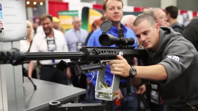 gun enthusiasts look over firearms at the barrett firearms manufacturing booth during the nra annual meetings & exhibits on may 21, 2016 in... - exhibition stock videos & royalty-free footage