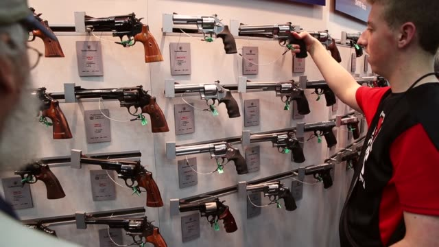 gun enthusiasts look over firearms at the smith & wesson booth during the nra annual meetings & exhibits on may 21, 2016 in louisville, kentucky.... - 自衛点の映像素材/bロール
