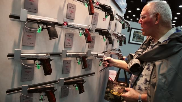 gun enthusiasts look over firearms at the smith wesson booth during the nra annual meetings exhibits on may 21 2016 in louisville kentucky about... - gun stock videos & royalty-free footage