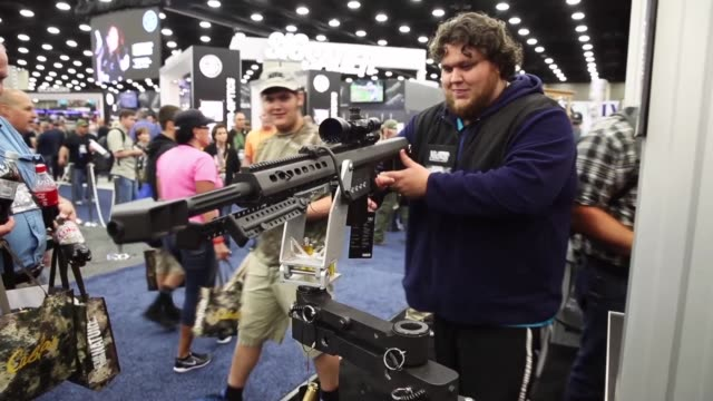 Gun enthusiasts look over firearms during the NRA Annual Meetings Exhibits on May 21 2016 in Louisville Kentucky About 80000 visitors are expected to...