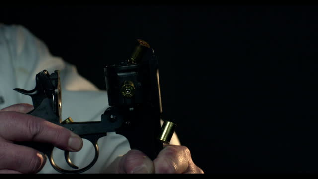 A gun is opened and empty cartridges fall to the ground in slow motion
