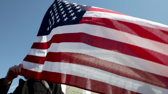 a gun rights advocate holds an american flag as he attends a rally organized by the virginia citizens defense league on capitol square near the state... - virginia stato usa video stock e b–roll