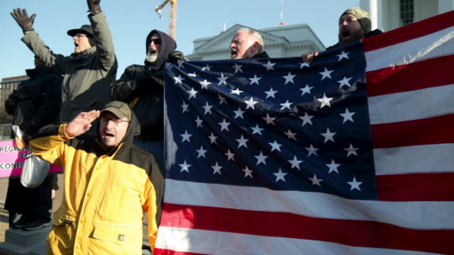 gun rights advocates hold an american flag as they attend a rally organized by the virginia citizens defense league near the state capital building... - virginia us state stock videos & royalty-free footage