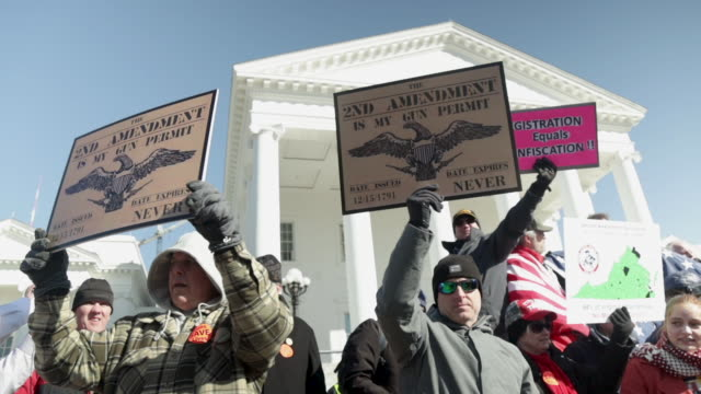 gun rights advocates hold signs as they attend a rally organized by the virginia citizens defense league on capitol square near the state capital... - virginia stato usa video stock e b–roll