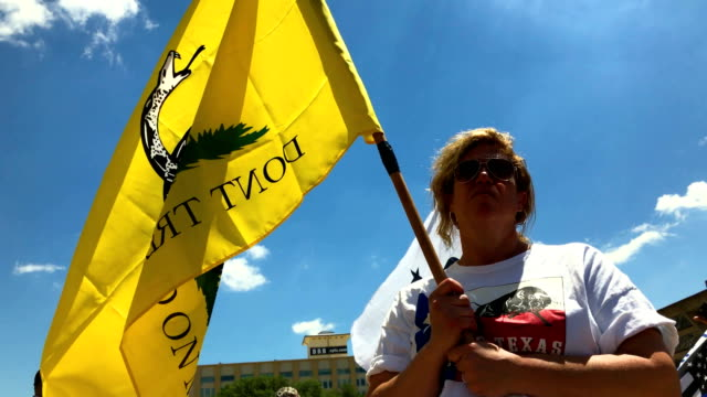 "a gun rights advocates holds a ""don't tread on me"" flag during a demonstration outside of dallas city hall near the nra annual meeting exhibits at... - national rifle association stock videos & royalty-free footage"