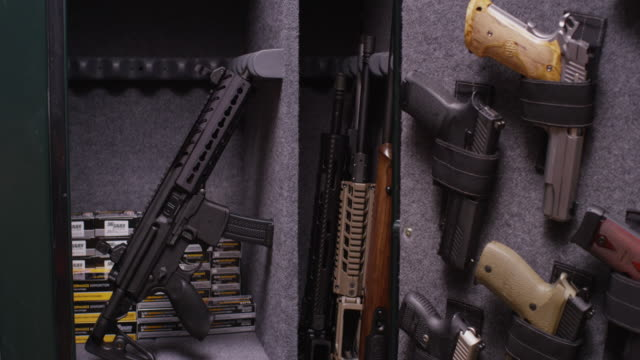 gun safe is opened to reveal a homeowners collection of hand guns, pistols, rifles, shot guns, ammunition, and an automatic weapon. - arma da fuoco video stock e b–roll
