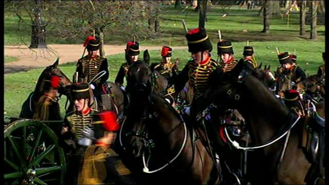 vídeos de stock, filmes e b-roll de gun salute in green park guns harnessed to horses / horses drag guns out of park / foot soldiers marching in park / military band marches out of park - parque green