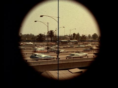 a gun sight aims at freeway traffic. - fadenkreuz stock-videos und b-roll-filmmaterial