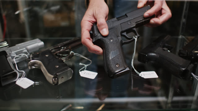 stockvideo's en b-roll-footage met gun store clerk pointing out firearm in display case - vuurwapenwinkel