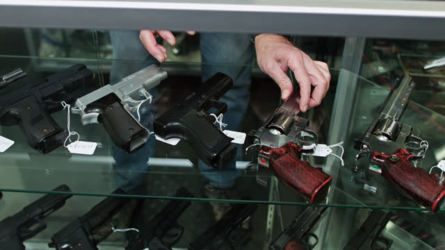 gun store owner adjusting handguns in display case - 銃器店点の映像素材/bロール