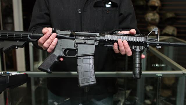 gun store owner holding out assault rifle - 銃器店点の映像素材/bロール