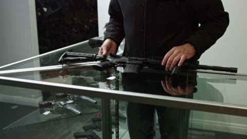 gun store owner putting price tag on assault rifle - 銃器店点の映像素材/bロール