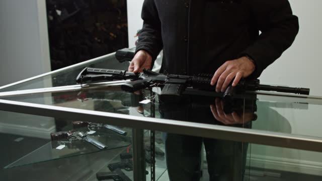 stockvideo's en b-roll-footage met gun store owner putting price tag on assault rifle - vuurwapenwinkel