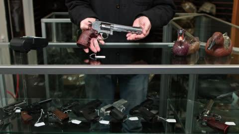 gun store owner showing product to customer - 銃器店点の映像素材/bロール
