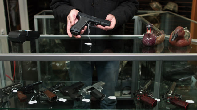 gun store owner showing products to viewer - gun shop stock videos & royalty-free footage
