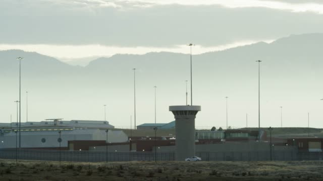 "gun towers and the exterior of the united states penitentiary, administrative maximum facility supermax prison complex in florence, colorado (fremont county) under the rocky mountains - the ""alcatraz of the rockies"" - federal prison building stock videos & royalty-free footage"