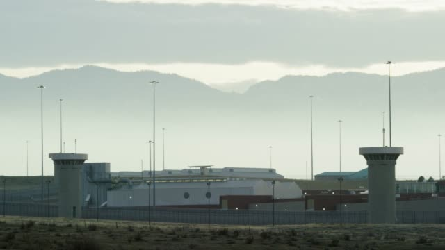 "gun towers and the exterior of the united states penitentiary, administrative maximum facility supermax prison complex in florence, colorado (fremont county) under the rocky mountains - the ""alcatraz of the rockies"" - prison stock videos & royalty-free footage"