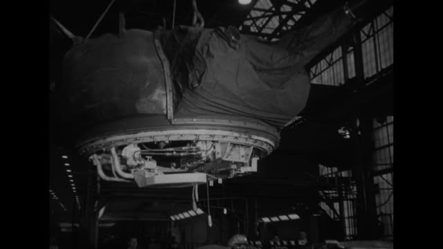 Gun turret suspended from roof of factory is lowered onto body of tank / Note exact day not known