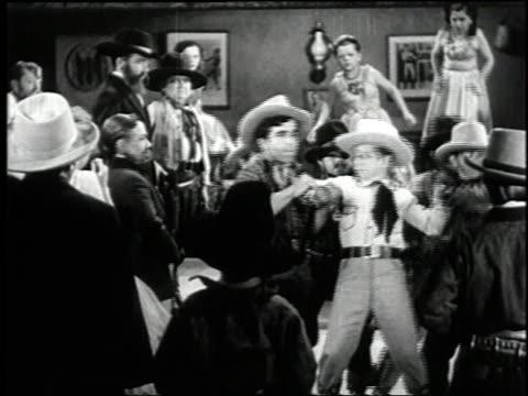 vídeos de stock, filmes e b-roll de 1938 montage gunfight in the saloon in the film 'terror of tiny town' / united states - faroeste