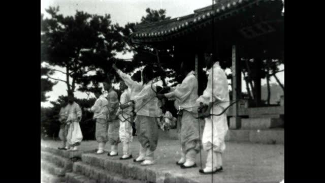 vídeos y material grabado en eventos de stock de gungsul, korean archery, using the gakgung bow. this clip shows archers demonstrating their craft from an original burton holmes film. - coreano oriental