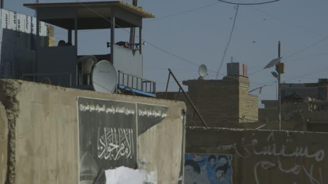 Gunman in guard tower in Baghdad, wide shot