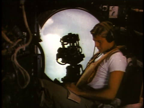vídeos de stock e filmes b-roll de gunner peering past machine gun out porthole, then reading book / crew reading, smoking, eating / navigator setting course - pacific war