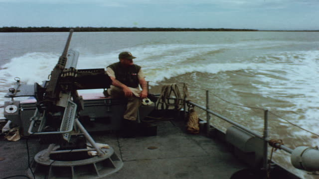 gunner sitting on ammo box beside sternmounted 81mm mortar on swift boat underway wake flowing out behind during operation jackstay / vietnam - mekong delta stock videos & royalty-free footage
