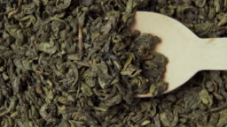Gunpowder Green Chinese tea close-up. Wooden dessert spoon scoops dried rolled leaves
