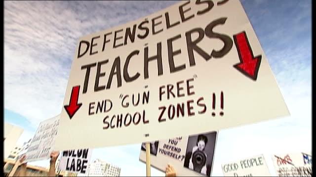 vídeos y material grabado en eventos de stock de texas has some of the most lax gun regulations low angle view 'defenseeless teachers end gun free school zones' tilt down man holding placard - placard